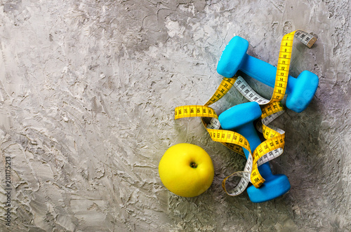 Turquoise dumbbells with measuring tape and yellow apple on concrete background. Free space for your text. Sport concept