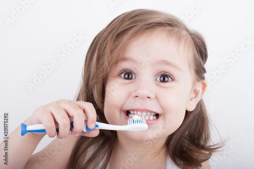 Leinwanddruck Bild Cute little girl brushing her teeth