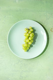 Bunch of ripe green grapes on turquoise plate over green pastel pin-up background. Copy space. Top view
