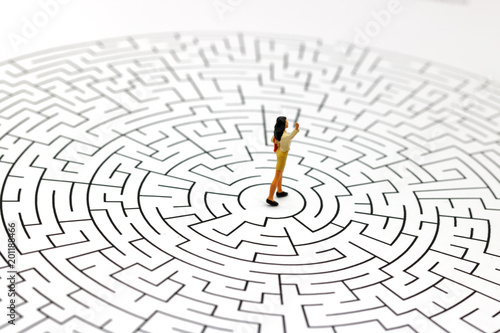 Miniature people: Businesswoman standing on center of maze  Concepts