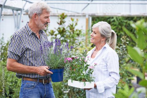 Foto Murales Mature Couple Choosing Plants At Garden Center