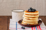 Stack of homemade fluffy pancakes in a plate with berries and white jar.  Rustic style. Wooden background. Copy space. - 201196082