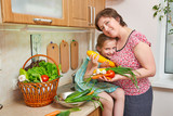 Mother and daughter with basket of vegetables and fresh fruits in kitchen interior. Parent and child. Healthy food concept