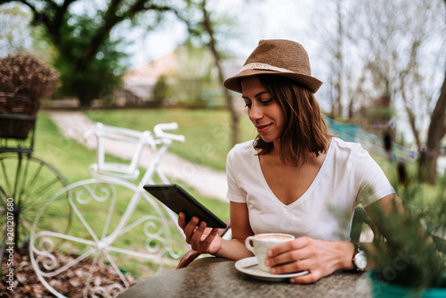 Beautiful young woman using tablet outdoor in cafe garden.