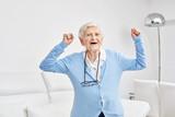 Seniorin jubelt mit geballten Fäusten - 201208474