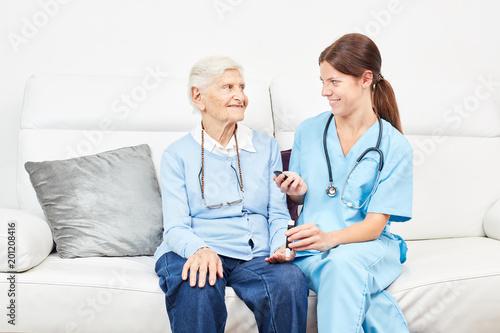 Foto Murales Krankenschwester misst Blutzucker bei Seniorin