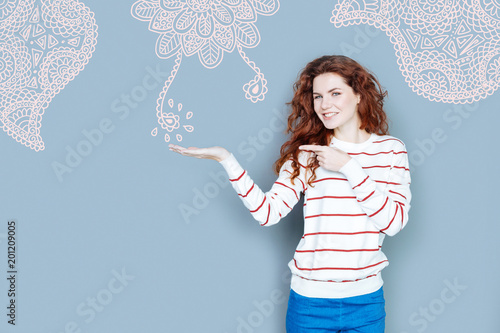 Foto Murales Lovely ornament. Cheerful experienced painter smiling while showing her amazing new ornament on the wall