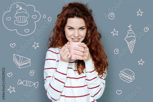 Nowa dieta. Entuzjastyczny student pozytywny uśmiechając się podczas picia ziołowej herbaty podczas jej diety