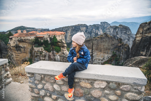 Girl Sitting on Cement Fence
