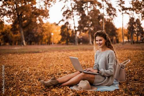 Girl working on laptop in the autumn park. Freelance work concept.