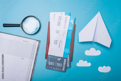 Foto Murales Air tickets with passport and paper plane on blue background, topview. The concept of air travel and holidays