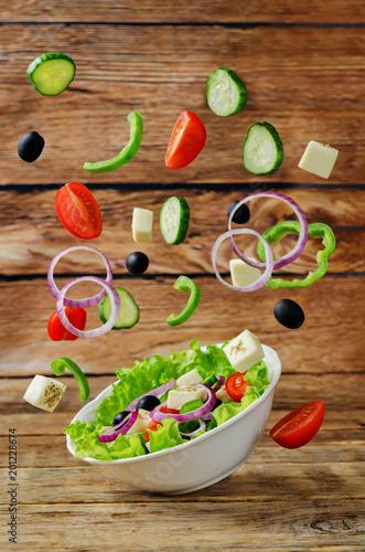 Greek Salad with flying ingredients to prepare it - 201228674