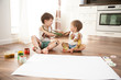 Two cute brothers paint each other in color.