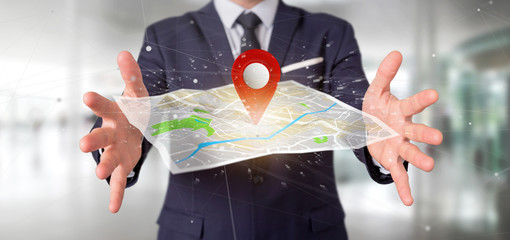 Businessman holding a 3d rendering pin holder on a map © Production Perig