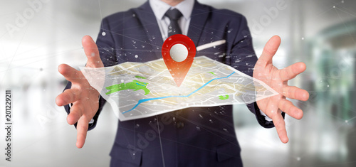 Foto Murales Businessman holding a 3d rendering pin holder on a map