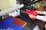 Young woman printing on cap at workshop