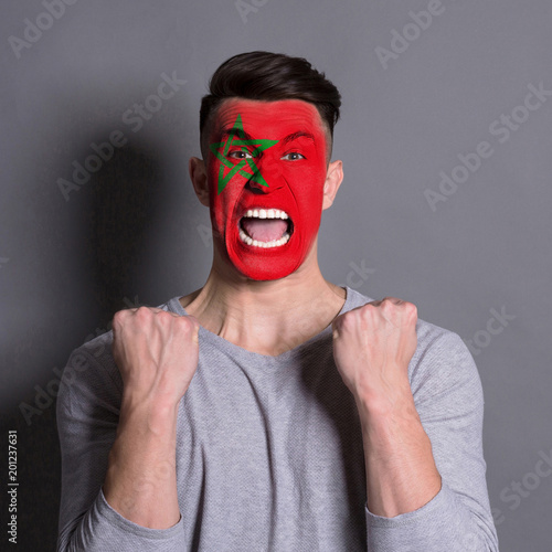 Young man with Morocco flag painted on his face