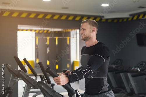 Poster Young man in gym ride stationery bike