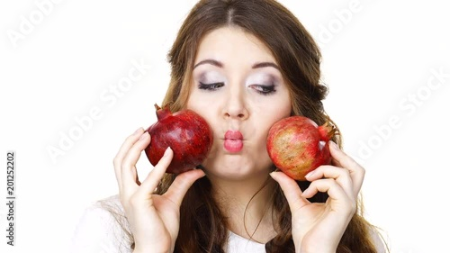 Joyful young woman playing with pomegranate fruits, isolated on white. Healthy eating, cancer prevention, immune support concept.