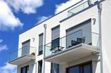 Moderne Balkone, verglast mit Metall-Geländer an Neubau-Hausfront mit Flachdach, Wasserkästen, Regenfallrohren und Edelstahl-Attika - 201254408