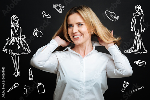 Fashionable look. Emotional young cheerful woman feeling satisfied with her amazing haircut and smiling while touching her hair