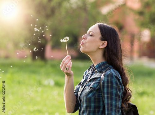 Woman blowing dandelion flower