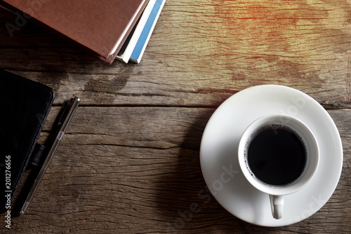Book, pen, leather bag and coffee cup on wooden floor. - 201276656
