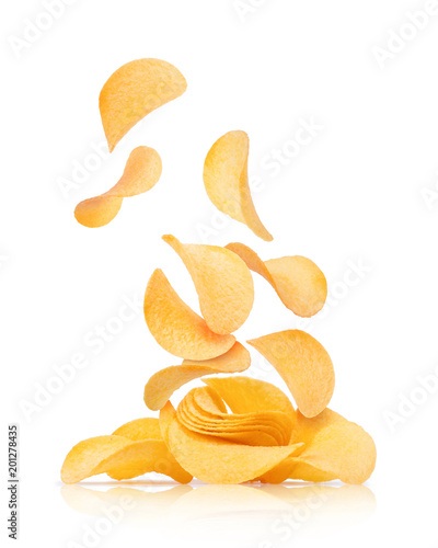 Potato chips fall on a heap with chips on a white background