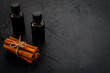 Cinnamon oil for cooking, aromatheraphy, skin care. Bottles near cinnamon sticks on black background space for text