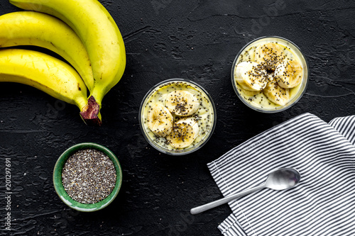 Sticker Banana pudding with chia seeds as low-calorie tasty appetizer. Black background with blue tablecloth top view closeup