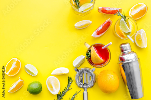 Mix exotic fruit cocktail with alcohol. Shaker and strainer near citrus fruits and glass with cocktail on yellow background top view space for text - 201298250