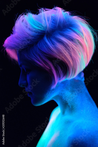Model young beautiful girl portrait in studio with creative makeup, in neon ultraviolet lamp. Glows in the dark. Hair coloring with neon paints. Body art is blue, green, orange. - 201312648