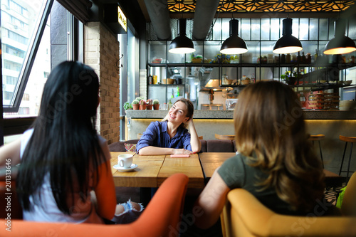 Cheerful women sitting at cozy cafe, smiling and drinking coffee. Concept of friendship and urban life.