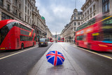 London, England - British umbrella at busy Regent Street with iconic red double-decker buses and black taxies on the move
