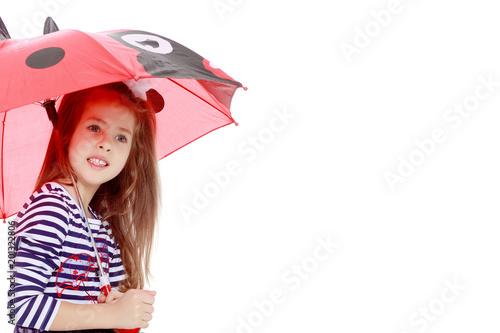 Little girl hiding under an umbrella.