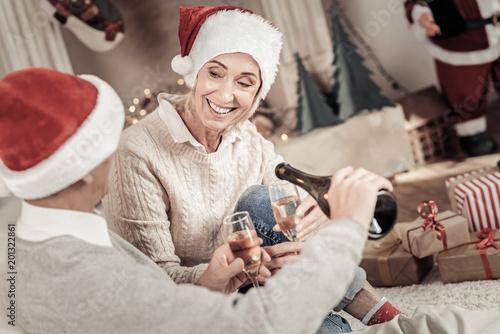 Drinking champagne. Pretty woman feeling happiness while drinking champagne, celebrating Christmas