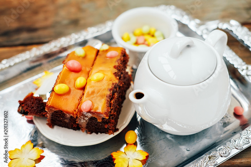 Autumn sweet dessert. Pumpking chocolate cake with dragee and tea