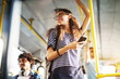 Young adorable joyful woman is standing on the bus using the phone and smiling.