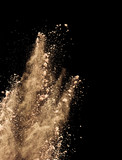 Abstract colored brown powder explosion isolated on black background. - 201348263