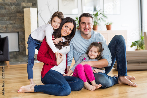 Portrait of a young family with two children at home.