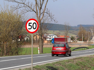 Limiting the speed of traffic to 50 km/h. Road sign on the highway. safety of traffic. Motor transportation of passengers and cargoes. Modern cars. The car is moving along the road.