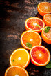Fresh raw blood oranges, halves, with mint, on dark rusty background copy space