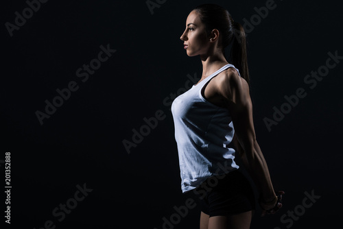 beautiful athletic sportswoman stretching arms, isolated on black - 201352888