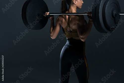 back view of female bodybuilder posing with barbell, isolated on grey - 201353237
