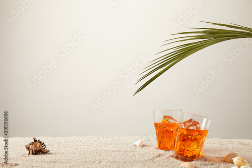 close up view of cocktails with ice with fern and seashells on sand on grey background