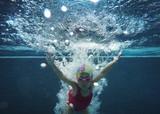 happy asian kid swimming underwater in summer.