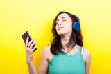 Dreammy young woman listening to music with a smartphone in hands on yellow background in studio - 201359808