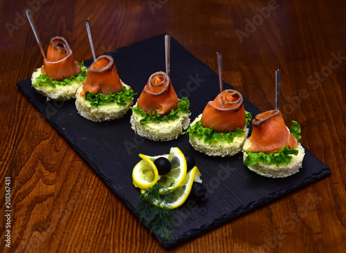Foto Murales Cold appetizers, canape with red fish, wooden background. Canape with salad leaves, red fish, lemon and dill. Delicious snacks served in restaurant on black dishes. Restaurant dish concept.