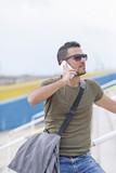 Urban man using a phone wearing sunglasses outdoors - 201369412