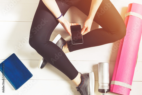 Poster Female fitness concept. Girl in sportswear, holds phone in hand on a white floor.